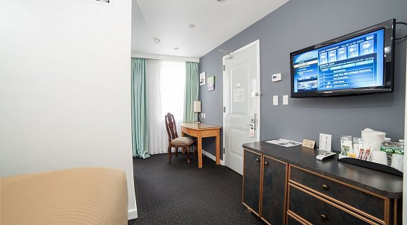 Photo 1 of Deluxe King Room with a king sized bed, view of the lower west side, and all the standard amenities.