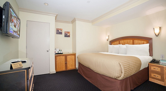 Photo 3 of Deluxe King Room with a king sized bed, view of the lower west side, and all the standard amenities.