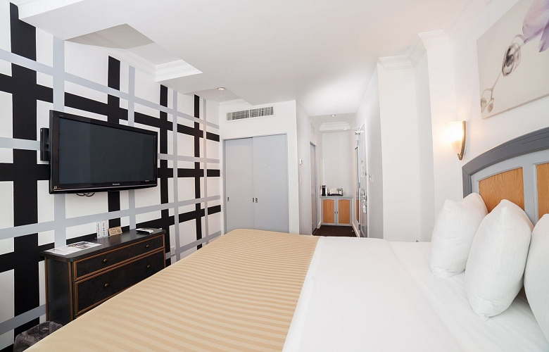 Photo 1 of Deluxe King Room with City View with a  king sized bed, view of the lower west side, and all the standard amenities.